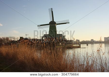 Old Dutch Windmills Made Of Wood Built Along The Water Stream Of The Zaan River At Sunset Time With