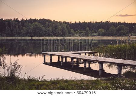 Wooden Pier At A Calm Lake At Sunset, Color Toning Applied.