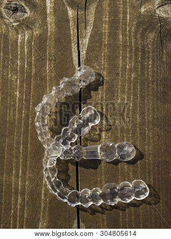 Transparent Dental Retainer Or Clear Retainer, Braces. Invisible Aligner On The Table Wooden