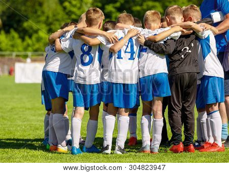 Football Youth Team Huddling With Coach. Young Happy Boys Soccer Players Gathering Before The Final