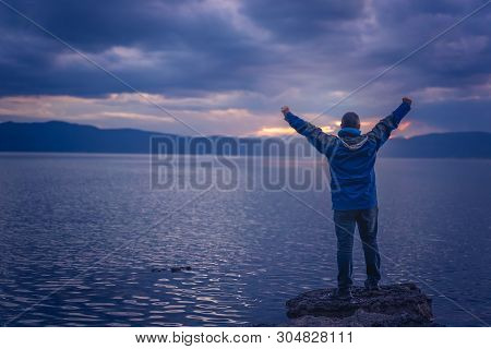 Triumphant Man Lifting His Hands High In The Air While Standing On The Large Boulders On The Shore O