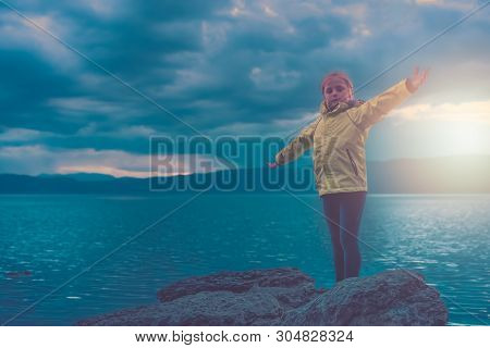 Triumphant Little Girl Lifting Her Hands High In The Air While Standing On The Large Boulders On The