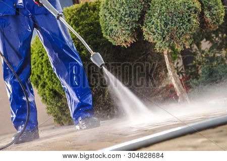 Men Washing Garden Residential Brick Paths With Professional Pressure Washer