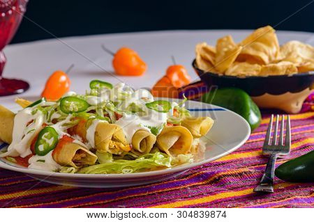 Flautas, Mexican Food, Chicken Rolled In Tortillas And Fried, Served With Tortilla Chips, Spicy Sauc