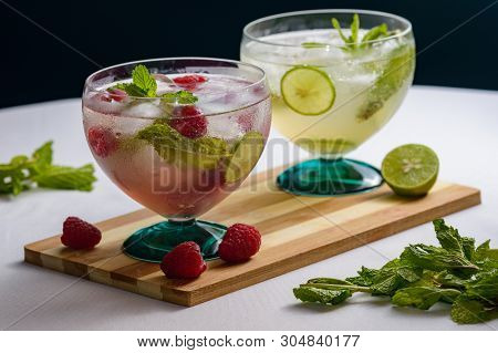 Raspberry Mojito And Mojito Rum Cocktail Drinks With Ingredients, Limes, Lemons, Mint, Brown Sugar A