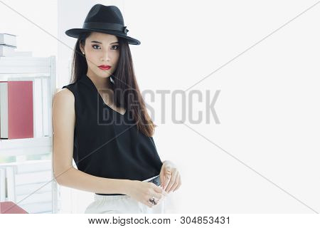 Sexy Asian Model Woman In Black Shirt And White Pants, Wearing Hat, Standing And Pompous, Studio Sho