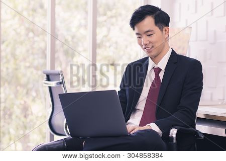 Handsome Asian Businessman Standing And Using Laptop In Office.