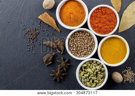 Spices In Little White Bowls On Black Slate Background - Indian Spice Top View Photo With Space For