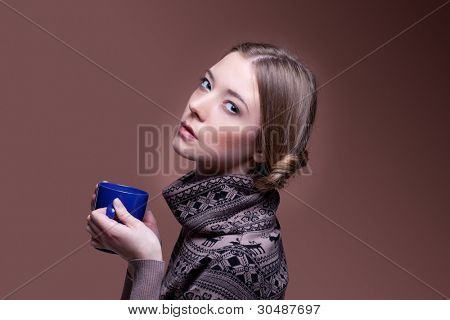 Beautiful happy young woman in a winter sweater with cup of aromatic coffee