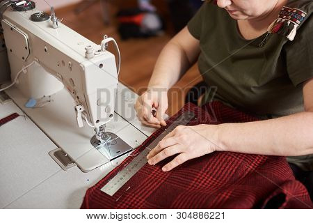 Tailor Measuring Plaid Red Textile With Ruler, Fixing Edges Of Fabric With Pins. Preparing Textile F