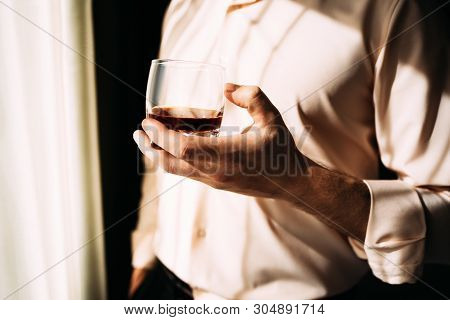 Young Man With Glass On Whiskey Near Window. Man Drinking Whiskey At The Window. Drink Whiskey, Cogn