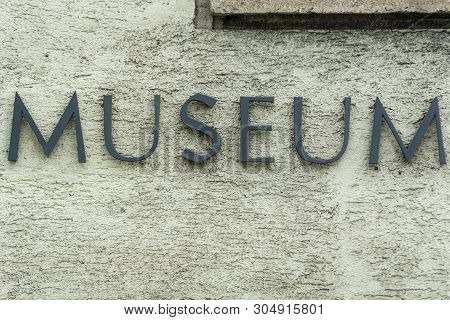 Weathered Metal Museum Sign On Plaster Wall