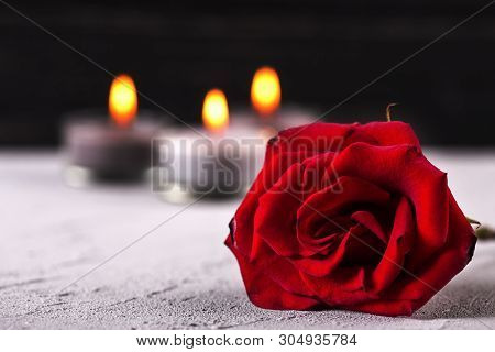 Mourning Concept. Close Up Of  Red Rose And Burning Candles On Grey Textured Background. Card For Mo
