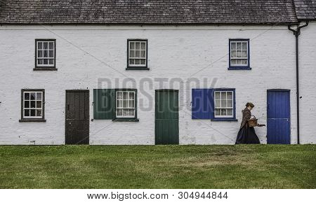 Belfast, Northern Ireland  - July 31: Woman In Period Costume Walking In Front Of 19th Century Row H