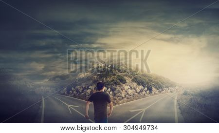 Rear View Man Walking In Front Of Crossroad As Road Is Split In Two Different Ways. Choosing The Cor