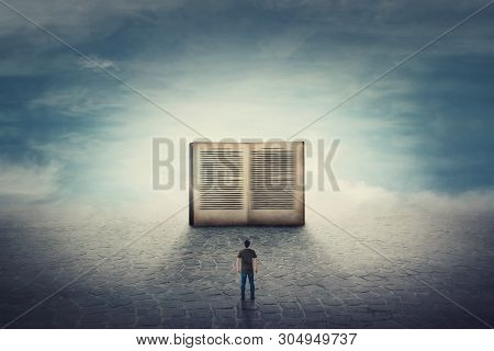 Surreal Scene As Student Guy Stands On A Pavement Road In Front Of A Giant Opened Book. The Importan