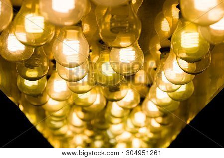 Closeup Of Several Yellow Gold Lightbulbs Shining In The Dark.