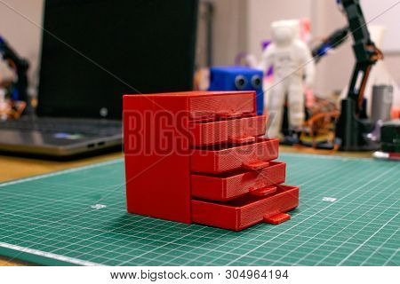 Kropivnitskiy, Ukraine - 12 may, 2018: 3D printed red plastic dresser on the background of laptop and devices. Furniture model printed on automatic three dimensional 3d printer. poster