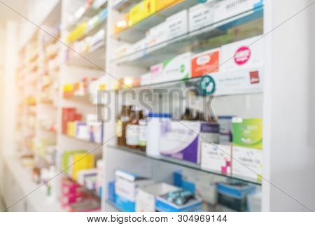 Blurry View Of Drug Store And Pharmacist. Blurred Clean Pharmacy With Medicine On Shelves. Defocus W