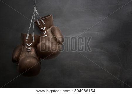 Boxing gloves hanging on blackboard