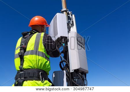 Telecommunication Engineer  In Helmet And Uniform Installs Telecomunication Equipment In His Hand An