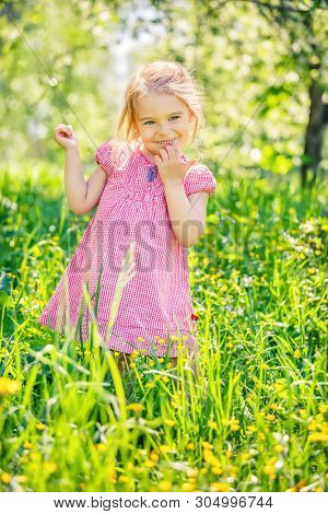 Happy little girl playing in sunny spring garden