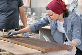 Middle-aged craftswoman working in woodworking workshop. Female varnishing wooden board with oil, varnish. Furniture joinery wood business. poster