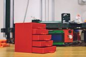 3D printed red plastic dresser on the background of three dimensional 3d printer. furniture model printed on automatic three dimensional 3d printer poster