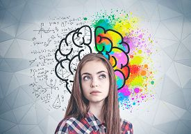 Thoughtful Young Woman In Casual Clothes Standing Near Geometric Pattern Wall With Colorful Brain Sk