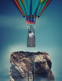 Ladder To The Top Of A Mountain Rock And A Man Looks Through Binoculars Flying With Hot Air Balloon.