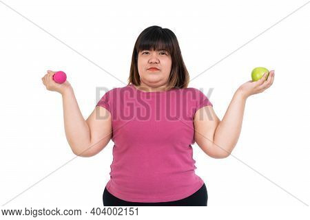 Overweight Asian Woman Sitting And Holding A Green Apple And Dumbbells On Isolated White Background.