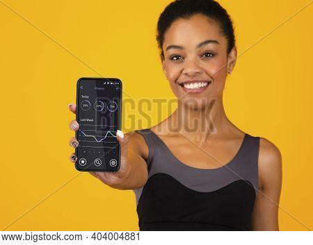 Black Woman Showing Phone With Fitness Progress Tracker App On Screen Posing Standing Over Yellow St