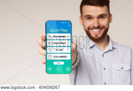 Guy Showing Smartphone With Sport Plan Application Posing Standing Over Gray Studio Background. Weig