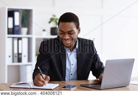 Smiling African American Entrepreneur Having Online Training In Office, Using Laptop, Taking Notes,
