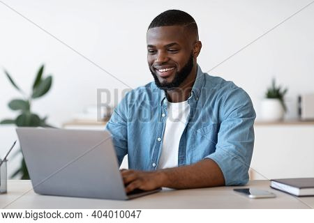 Remote Work. Handsome Black Freelancer Guy Working On Laptop At Home Office, Sitting At Desk With Co
