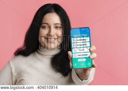 Overweight Lady Showing Phone With Sport Plan Application With Workout Calories Counter Posing Stand