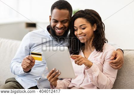 Online Shopping And Ecommerce. Happy Young African American Family Of Two People Sitting On Sofa At