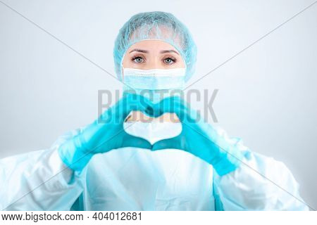 A Nurse In A Medical Gown And Mask Makes A Heartfelt Gesture With Her Fingers