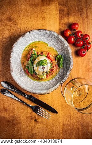 Burrata italian cheese snack with tomatoes served on white plate