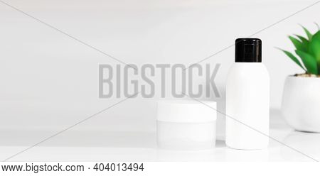 Skincare Cosmetics Bottles On White Background, With A Green Plant. Spring Season Cosmetics. Daily C