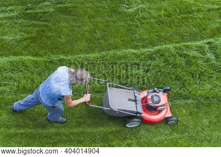 Lawn Mower Is Cutting Green Grass Cut, The Gardener With A Lawn Mower Is Working In The Backyard, To