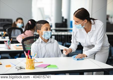 Hygiene And Cleaning. Teacher Cleaning Table With Antibacterial Sanitizer And Napkin, Disinfecting S