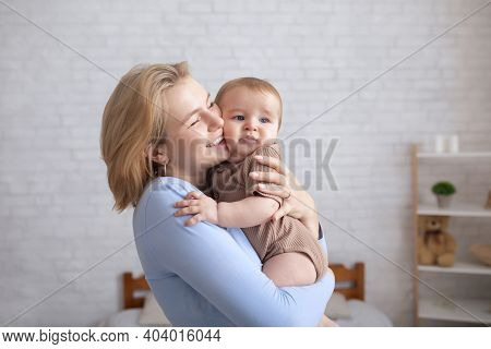 Happy Loving Mother Blonde Woman Holding And Kissing Sweet Little Baby Girl, Young Mom And Adorable