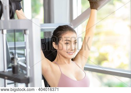 Beautiful Young Sport Woman Exercising In Gym By Using Shoulder Press Machine With Smile Face Happy