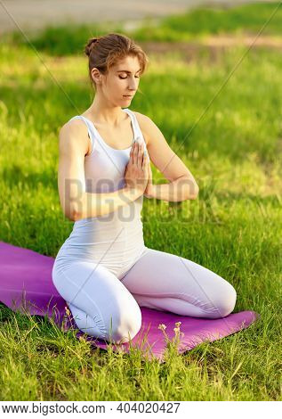 Strong Young Fitness Woman Meditate On Green Grass. Morning Meditation. Female On A Yoga Mat To Rela