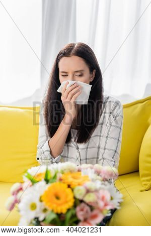 Allergic Woman Wiping Nose With Paper Napkin Near Bouquet On Blurred Foreground