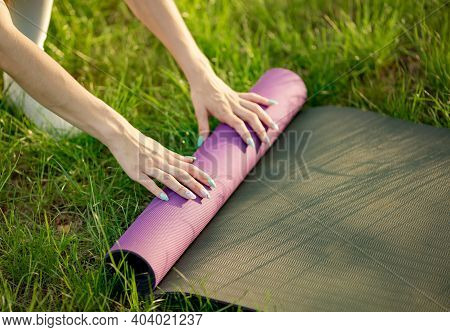 Woman Hands Rolling Or Folding Yoga Mat, Warm Tone. Cropped Image Of Female Putting Yoga Mat On Gras