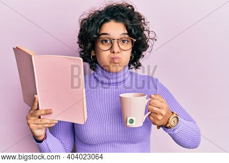 Young hispanic woman with curly hair reading a book and drinking a cup of coffee puffing cheeks with funny face. mouth inflated with air, catching air.
