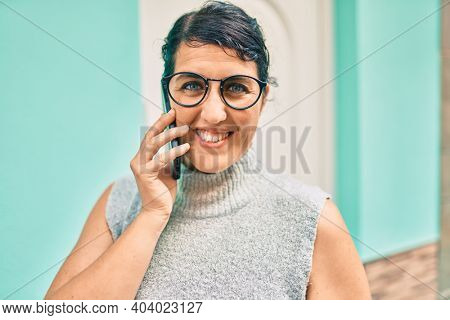 Young plus size woman smiling happy talking on the smartphone at the city.