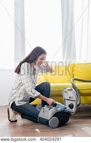 Allergic Woman Wiping Nose While Changing Dust Bag In Vacuum Cleaner